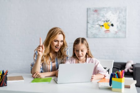 Selective focus of smiling woman having idea while using laptop near kid and stationery on table