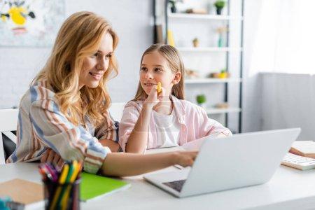 Photo pour Concentration sélective de la femme souriante en utilisant un ordinateur portable près d'un enfant tenant un stylo pendant l'éducation en ligne - image libre de droit