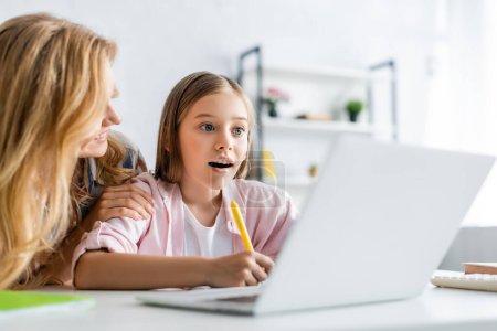 Photo pour Concentration sélective de la femme souriante embrassant fille écriture sur ordinateur portable pendant l'éducation en ligne à la maison - image libre de droit