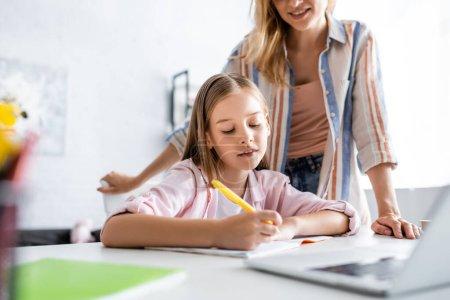 Photo pour Concentration sélective de la mère souriante debout près de sa fille écrivant sur un portable près d'un ordinateur portable sur une table - image libre de droit