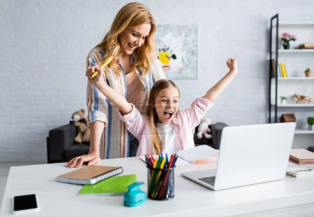 Photo for Selective focus of smiling mother looking at cheerful kid showing yeah gesture during online education - Royalty Free Image