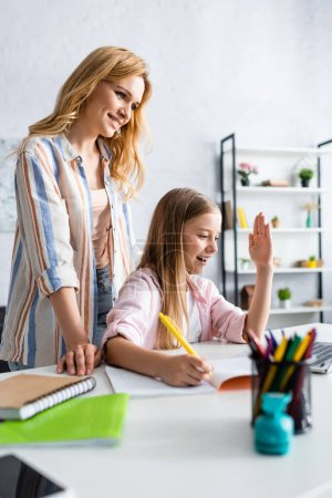 Photo for Selective focus of smiling woman standing near daughter during electronic learning - Royalty Free Image