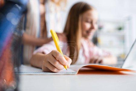 Photo pour Concentration sélective de l'écriture d'enfant sur le cahier pendant l'apprentissage électronique près de la mère - image libre de droit