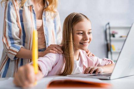 Photo pour Concentration sélective de la femme embrassant fille souriante écrit sur ordinateur portable près de chez soi - image libre de droit