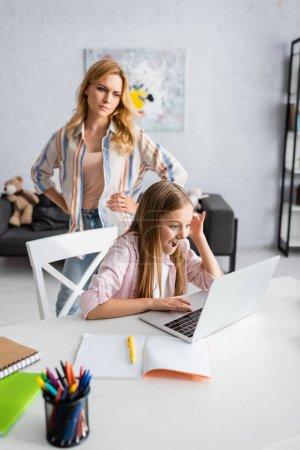 Photo pour Concentration sélective de la mère en colère debout près de l'enfant excité en utilisant un ordinateur portable près de la papeterie sur la table - image libre de droit