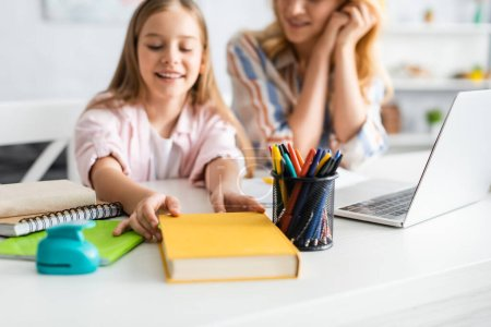 Selective focus of smiling kid taking book near mother and laptop on table