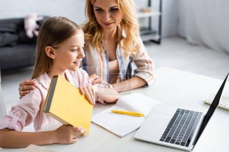 Photo pour Concentration sélective de la femme embrassant fille souriante tenant livre près de l'ordinateur portable et portable sur la table - image libre de droit