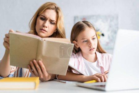 Photo pour Concentration sélective de la femme concentrée livre de lecture près de la fille en utilisant un ordinateur portable à la table - image libre de droit