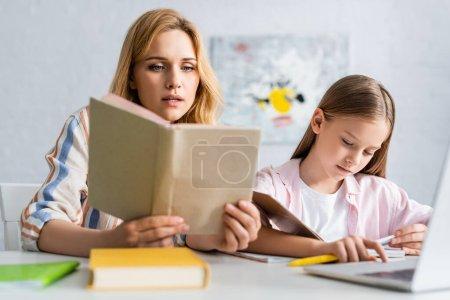 Photo pour Concentration sélective de livre de lecture de femme tout en aidant la fille pendant l'éducation en ligne à la maison - image libre de droit