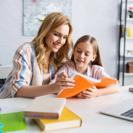 Photo for Selective focus of smiling mother and kid looking at notebook near laptop and books on table - Royalty Free Image