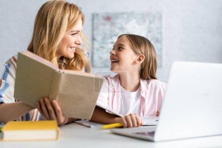Photo pour Concentration sélective de l'enfant joyeux regardant la mère avec le livre près de l'ordinateur portable à la table - image libre de droit