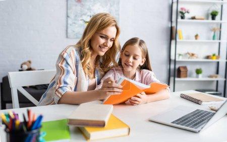 Photo pour Concentration sélective de la femme souriante tenant un cahier tout en aidant la fille pendant l'éducation en ligne à la maison - image libre de droit