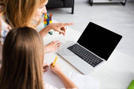 Photo pour Concentration sélective de la femme pointant du doigt un ordinateur portable près d'un enfant écrivant sur un ordinateur portable pendant l'apprentissage électronique à la maison - image libre de droit
