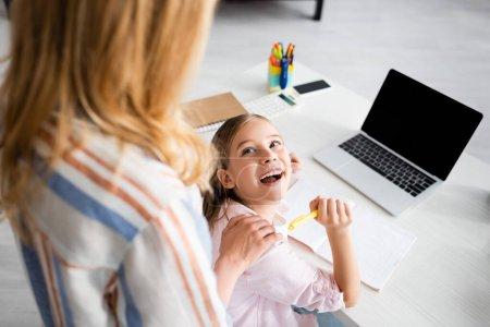 Photo pour Concentration sélective d'un enfant positif regardant sa mère tout en tenant un stylo près d'un ordinateur portable et d'un ordinateur portable sur la table - image libre de droit