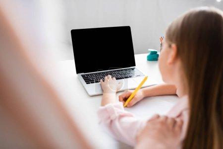Photo pour Concentration sélective de la mère debout près de sa fille en utilisant un ordinateur portable et en écrivant sur un ordinateur portable - image libre de droit