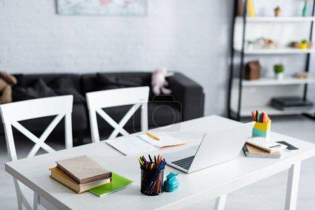Photo pour Concentration sélective de l'ordinateur portable, des livres et de la papeterie sur la table à la maison - image libre de droit