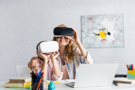 Selective focus of smiling woman embracing daughter while using virtual reality headsets near laptop and books