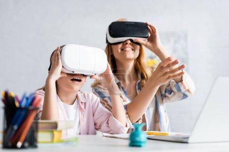 Photo pour Concentration sélective de l'enfant excité en utilisant vr casque près de la mère pendant l'éducation en ligne - image libre de droit