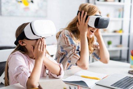 Photo pour Concentration sélective de l'enfant excité couvrant la bouche tout en utilisant des casques vr avec la mère près de l'ordinateur portable et de la papeterie - image libre de droit