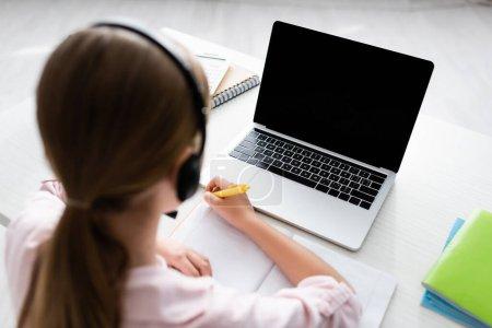 Photo pour Vue aérienne de l'enfant dans un casque d'écriture sur ordinateur portable pendant l'éducation en ligne à la maison - image libre de droit