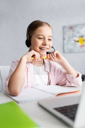 Photo for Selective focus of smiling child in headset holding pen and looking at laptop on table - Royalty Free Image