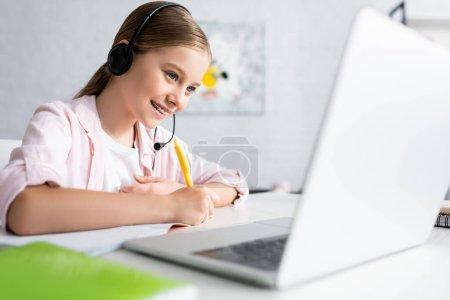 Photo pour Concentration sélective de l'enfant positif dans l'écriture casque sur ordinateur portable et à l'aide d'un ordinateur portable à la maison - image libre de droit