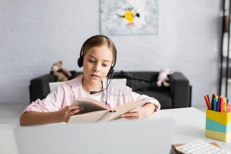 Photo pour Concentration sélective de l'enfant dans le livre de lecture du casque près de l'ordinateur portable sur la table - image libre de droit