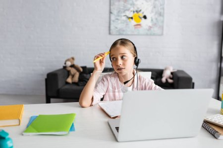 Photo for Selective focus of pensive child holding pen while using headset near laptop and stationery on table - Royalty Free Image