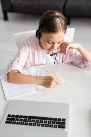 Photo pour Vue aérienne d'un enfant dans un casque d'écriture sur un ordinateur portable près d'une table - image libre de droit