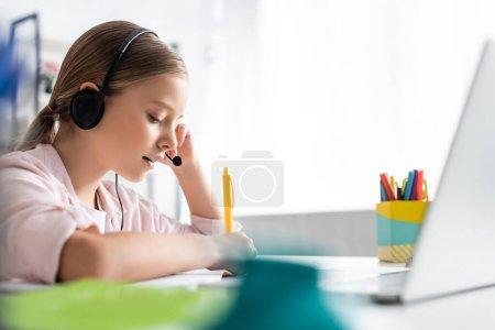 Photo pour Concentration sélective de l'enfant en utilisant un casque pendant l'apprentissage électronique à la maison - image libre de droit