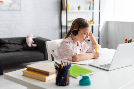 Photo pour Concentration sélective de l'écriture de l'enfant sur le carnet et en utilisant un casque près de l'ordinateur portable sur la table - image libre de droit