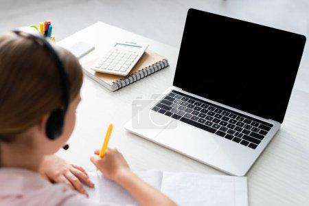 Photo pour Concentration sélective de l'enfant dans l'écriture du casque sur le portable près de l'ordinateur portable et la papeterie sur la table - image libre de droit
