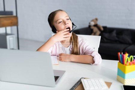 Photo pour Concentration sélective de l'enfant endormi dans le bâillement casque pendant l'apprentissage électronique à la maison - image libre de droit