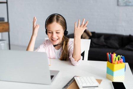 Photo pour Concentration sélective de l'enfant positif dans un casque regardant un ordinateur portable près de l'arrêt sur la table - image libre de droit
