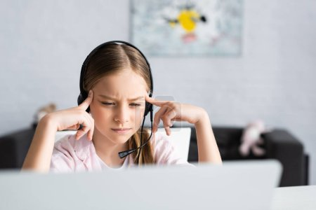 Selective focus of thoughtful kid in headset looking at laptop at home
