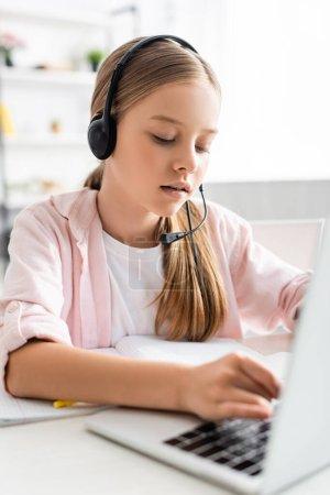 Photo pour Concentration sélective de l'enfant mignon dans la saisie de casque sur ordinateur portable près du portable sur la table - image libre de droit