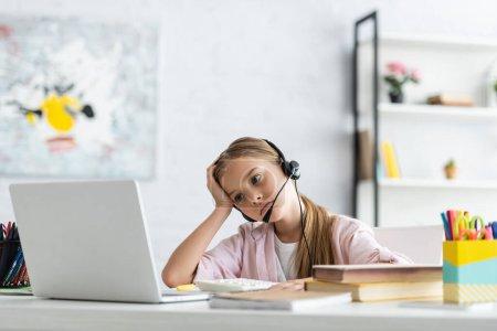 Photo pour Concentration sélective d'un enfant fatigué regardant un ordinateur portable tout en utilisant un casque près des livres sur la table - image libre de droit