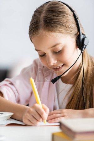 Selektiver Fokus des lächelnden Kindes in Headset-Schrift auf Kopierbuch am Tisch