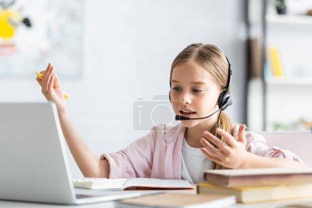 Photo pour Concentration sélective de l'enfant dans le casque parlant pendant le webinaire près des livres à la maison - image libre de droit