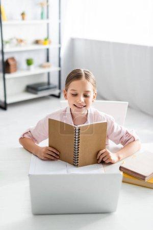 Photo pour Concentration sélective d'un enfant souriant tenant un cahier près d'un ordinateur portable et des livres sur la table - image libre de droit