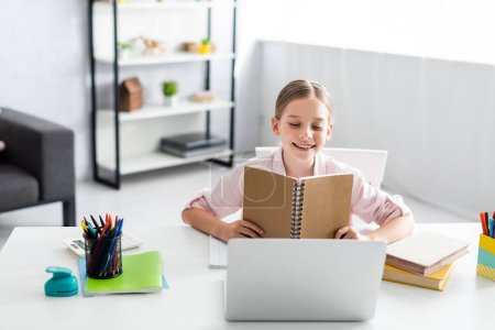 Photo for Selective focus of smiling kid holding notebook near laptop and books on table at home - Royalty Free Image