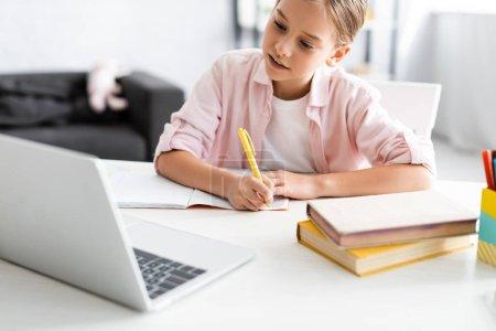 Photo pour Concentration sélective de l'écriture mignonne de l'enfant sur le carnet près des livres et de l'ordinateur portable pendant l'éducation électronique - image libre de droit