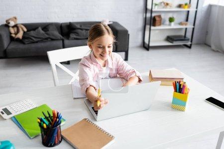 Photo pour Mise au point sélective d'un stylo souriant pour enfant et utilisation d'un ordinateur portable près des livres sur la table - image libre de droit