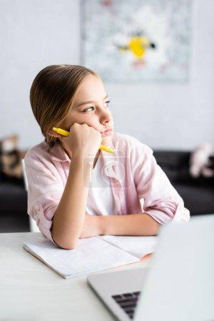 Photo pour Concentration sélective d'enfant rêveur avec stylo regardant loin près de l'ordinateur portable et le livre de copie sur la table - image libre de droit