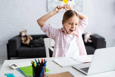 Photo pour Concentration sélective du bâillement et de l'étirement des enfants à côté de l'ordinateur portable et de la papeterie sur la table - image libre de droit