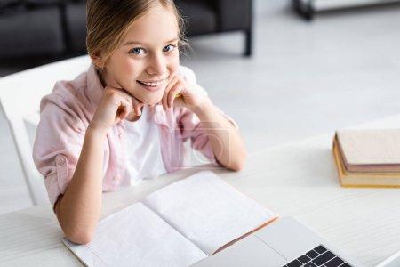 Photo pour Vue grand angle de mignon enfant souriant à la caméra près de l'ordinateur portable et le livre de copie sur la table - image libre de droit
