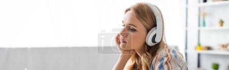 Panoramic shot of pensive woman using headphones