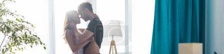 Photo pour Récolte panoramique de belle femme embrasser et déshabiller petit ami près de la fenêtre - image libre de droit