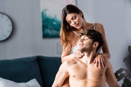 Photo pour Belle femme touchant beau copain torse nu dans la chambre - image libre de droit