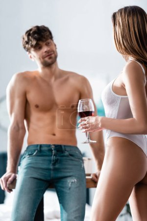 Photo for Selective focus of sexy woman holding glass of wine near shirtless boyfriend - Royalty Free Image